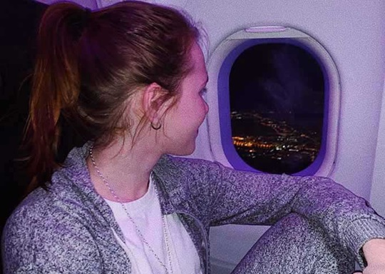 Student looks out the window of a plane