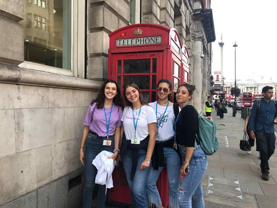 International students stand in front of a red London phone booth
