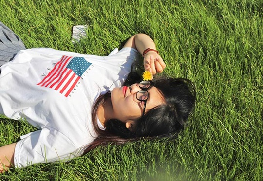 Educatius student laying in the grass wearing a shirt with the American flag