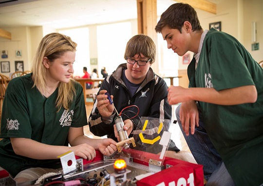 Three high school students building a robot in a classroom