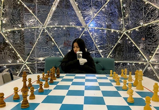 Educatius student sits in front of a giant chess board