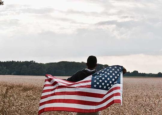 Học sinh chạy qua cánh đồng với lá cờ Mỹ trên tay