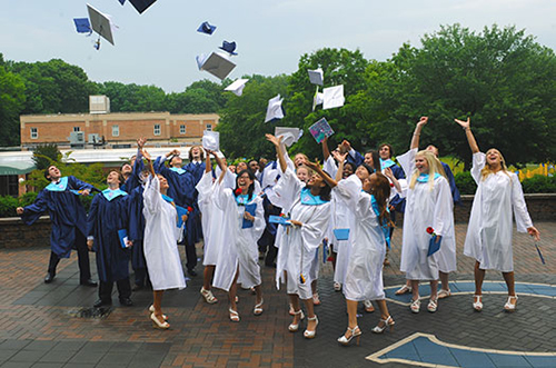 Calverton School graduates toss their caps in the air