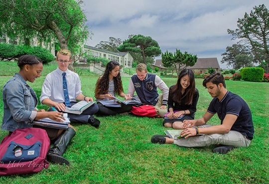 Học sinh học bài ở bãi cỏ trước sân trường nội trú
