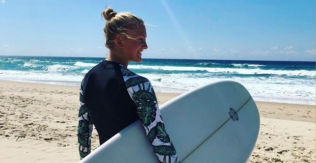 Utbytesstudent på strand med surfbräda