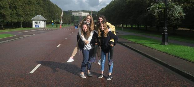 Fire utvekslingsstudenter poserer på ryggen til hverandre