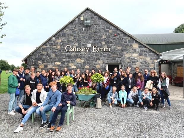 En stor gruppe utvekslingsstudenter foran en gammel steinbygning i Irland
