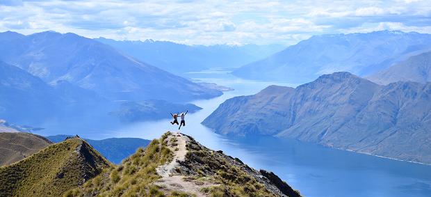 Paesaggio Neozelandese e due exchange student che saltano sulla vetta della montagna sullo sfondo