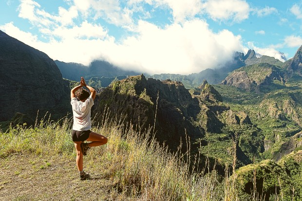 girl doing yoga in the mountains in reunion island