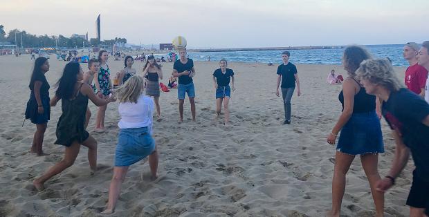 En gruppe ungdom spiller vollyball på stranden