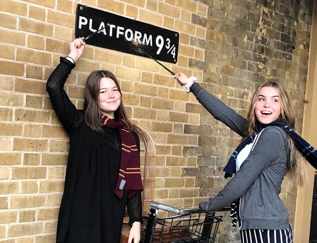 Utbytesstudenter vid plattform 9 och tre fjärdedelar vid King's Cross station i London