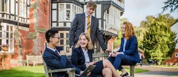 Fire utvekslingsstudenter sitter på en benk og smiler foran et gammelt bygg.