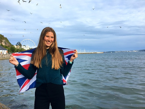 Utvekslingsstudent poserer med det britiske flagget på stranden