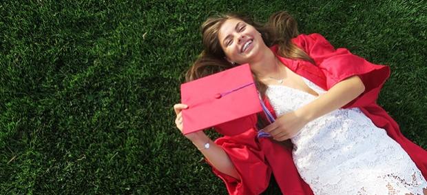 Exchange student con la toga rossa sul prato