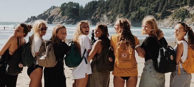 un gruppo di ragazze scambio culturale con l'anno in usa, di spalle davanti all'oceano pacifico