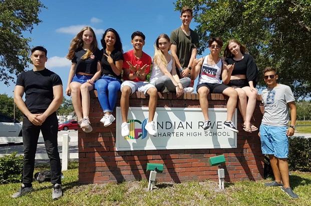 Studenter sitter på skole skiltet til Indian River high school i USA