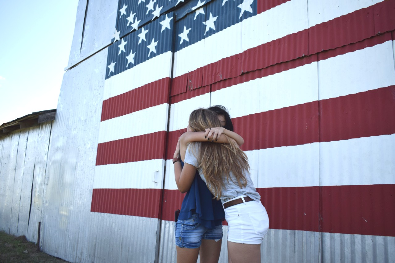 Exchange students hugging in front of an American flag