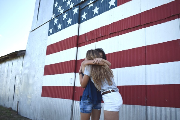 exchange students hugging in front of an american