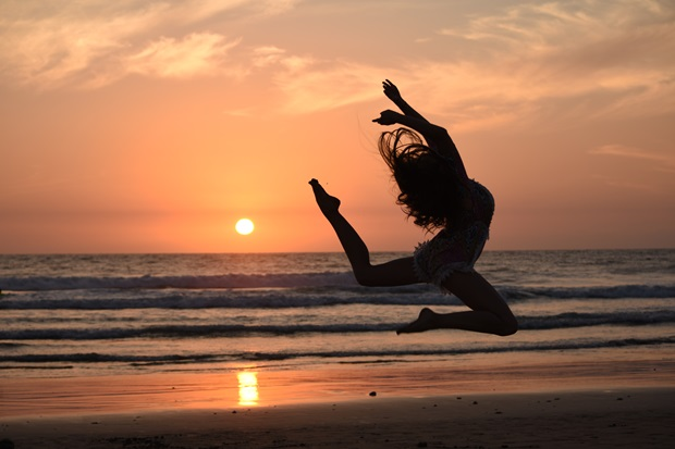 girl dancing at the beach in the sunset