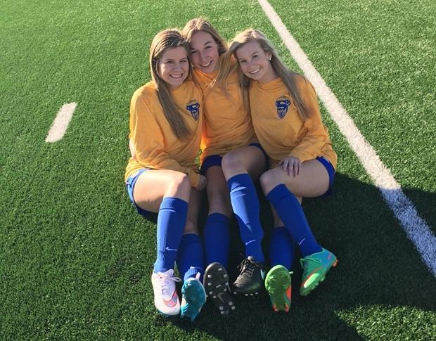 Tre fotbollsspelande studenter som sitter på en gräsplan