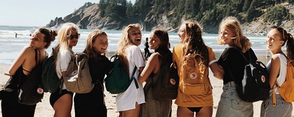 8-girl-students-standing-by-the-beach-with-backpacks
