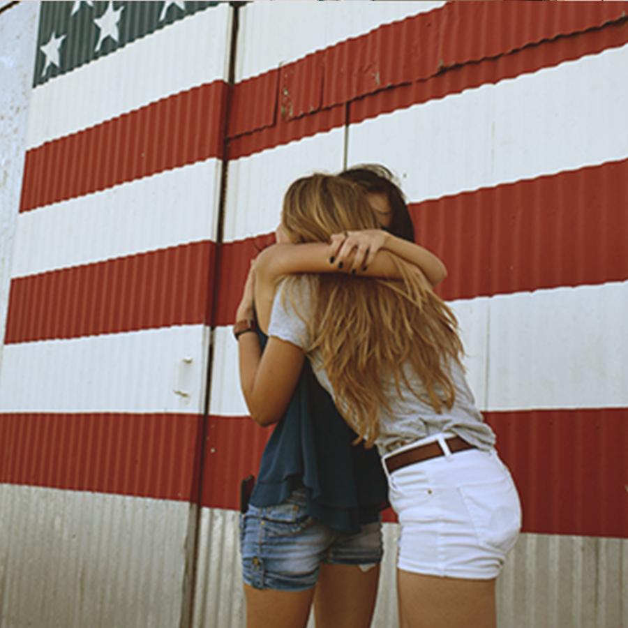 Kaksi vaihto-oppilasta halaa Yhdysvaltain lipun edessä