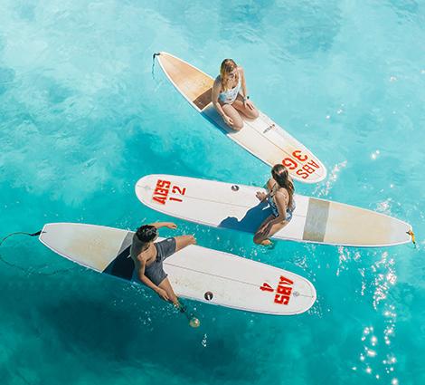 Tre studenter på surfbrädor i havet