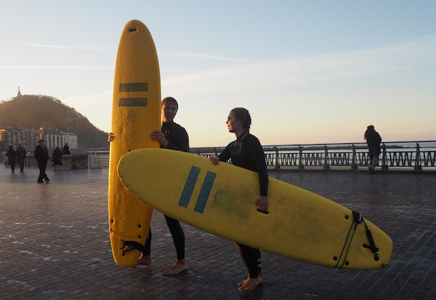 Kaksi surffaajaa lautojen kanssa espanjalaisella rannalla