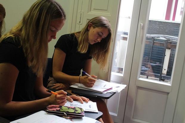 Vaihto-oppilas opiskelemassa espanjalaisessa koulussa kaverin kanssa