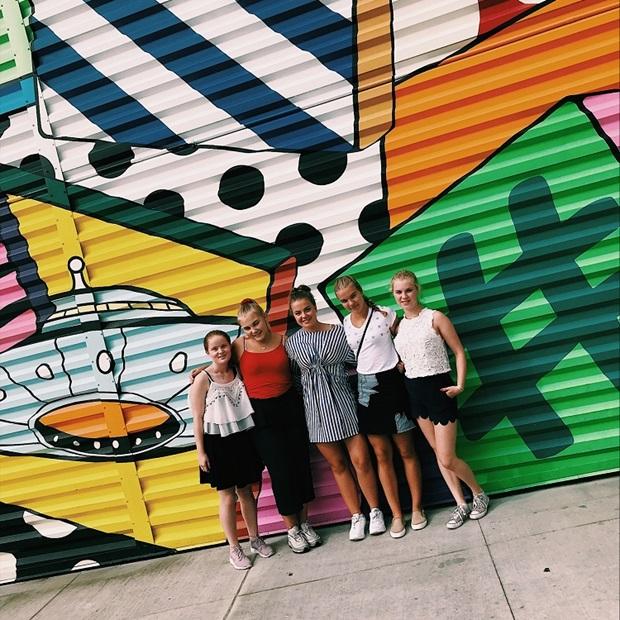 Vaihto-oppilaat graffitiseinän edessä New Yorkissa