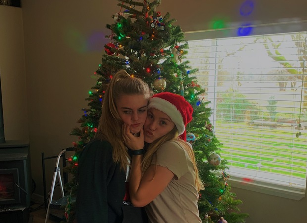 two girls in front of a christmas tree