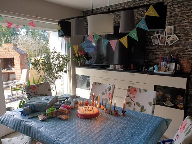Et spisebord er pyntet til en bursdagsfeiring, med blå duk, gaver og kake. Foto.