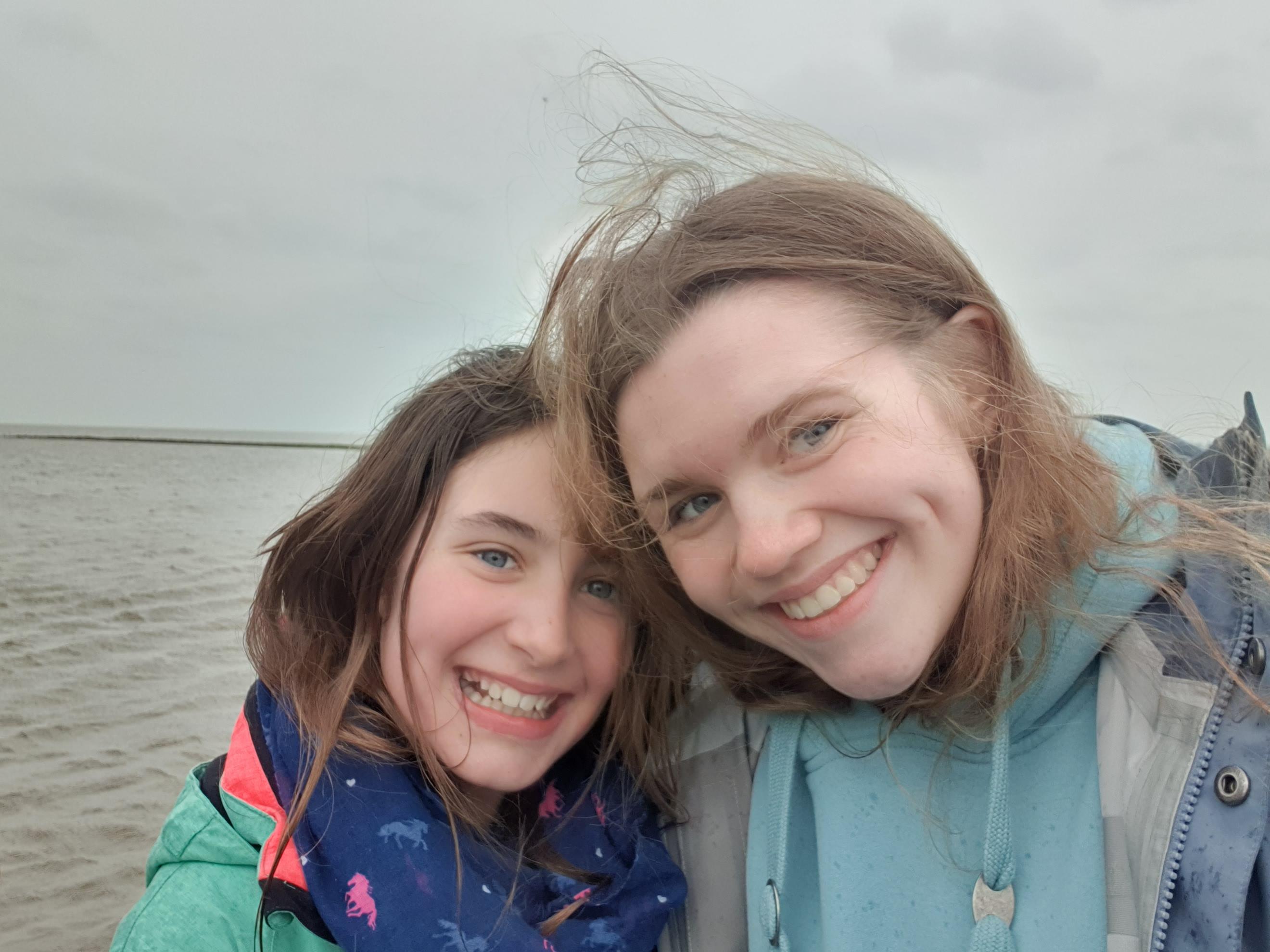 Nærbilde av to jenter som står ved et vann og smiler til kameraet. Foto.