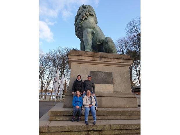 En vertsfamilie poserer foran en stor løvestatue