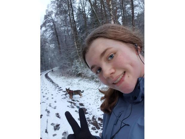 En utvekslingsstudent tar en selfie med en hund i bakgrunnen