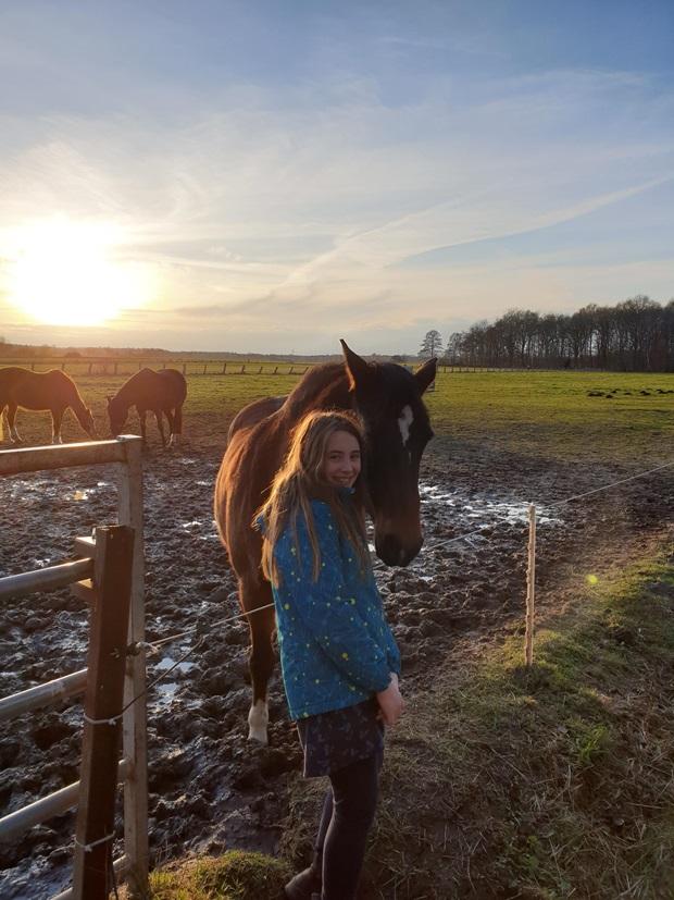 Ei jente smiler ved siden av en brun hest