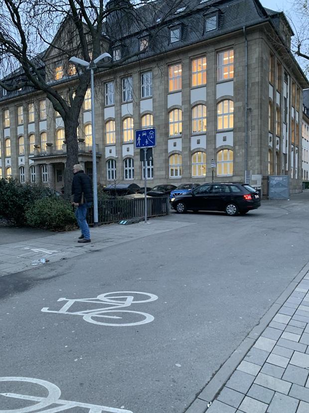 Deler av en stor bygning, en skole med en sykkelparkering foran seg