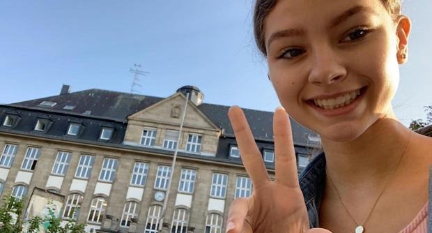 Utvekslingsstudent poserer med et peace tegn foran en stor bygning