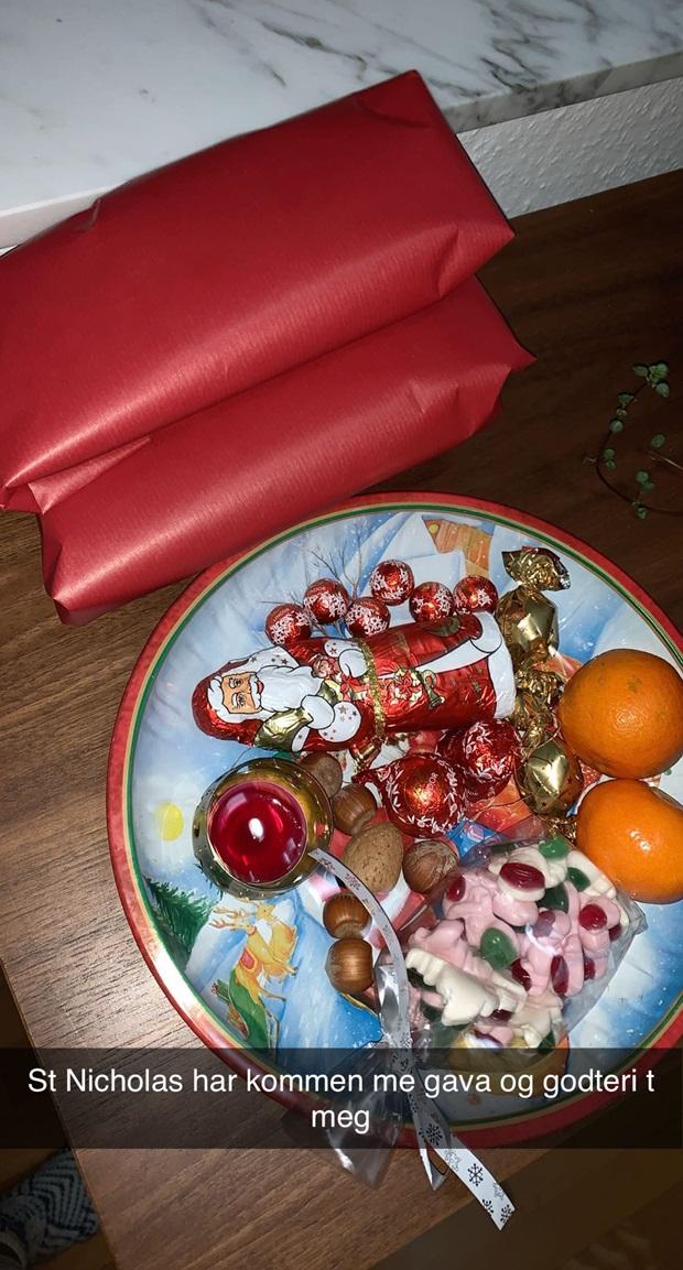 Et fant fylt med julegodteri og klementiner, og det ligger to røde pakker ved siden av fatet.