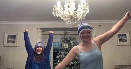 To utvekslingsstudenter i fotball-support klær smiler foran et juletre