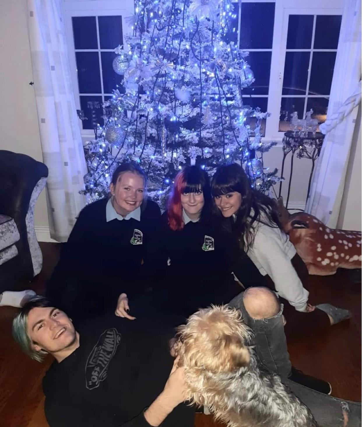 En gruppe venner sitter på gulvet foran et juletre som er dekorert med blå lys