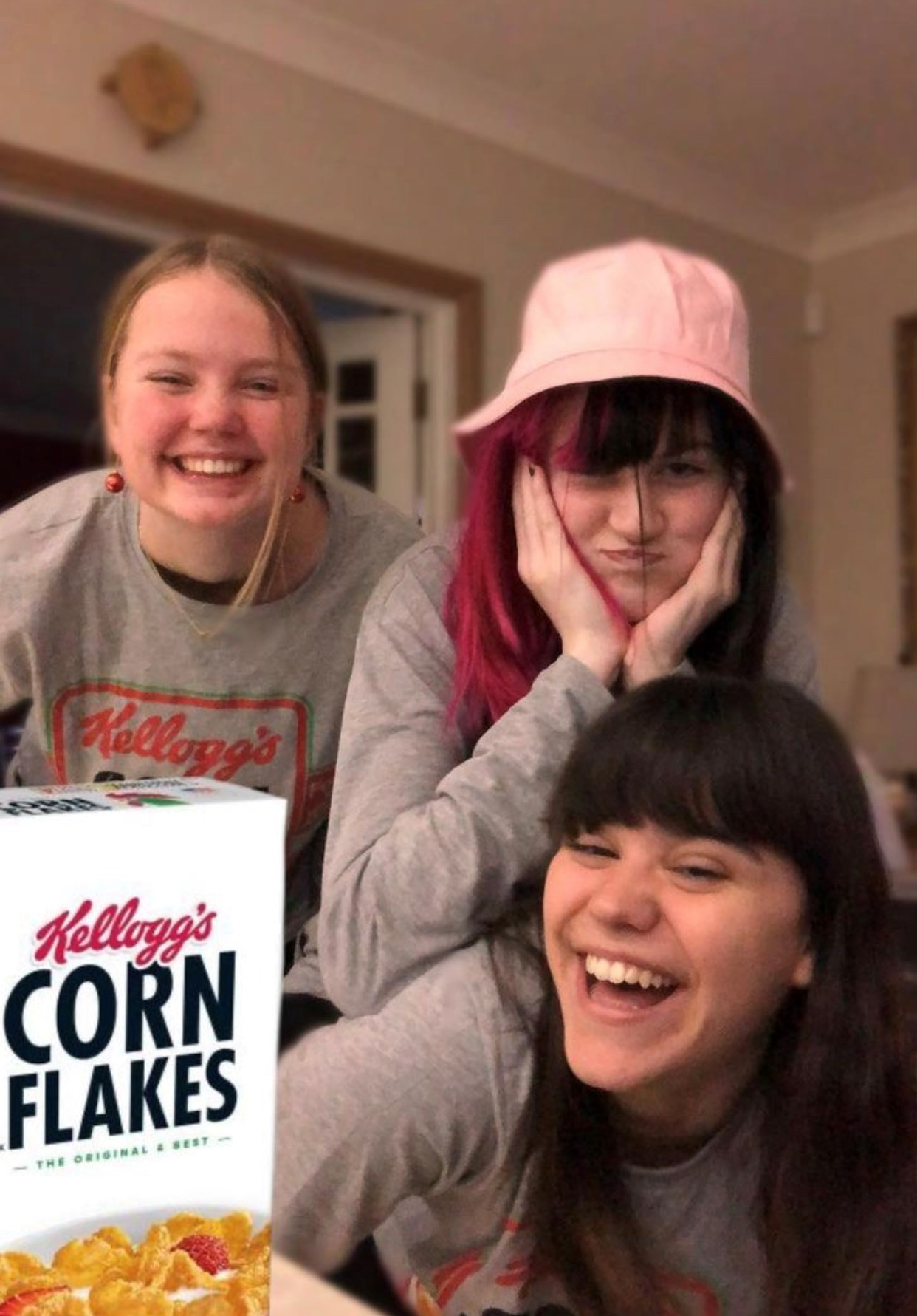 Tre jenter smiler og poserer med en Corn Flakes-eske