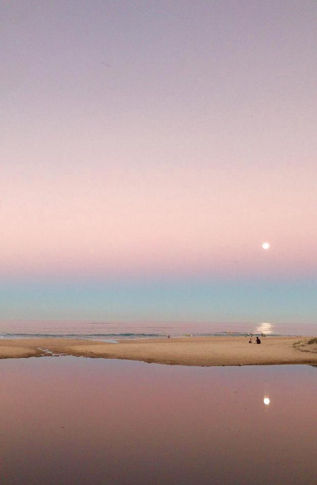 Rosa himmel speglas i havet