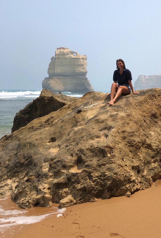 Utbytesstudent sitter på en klippa