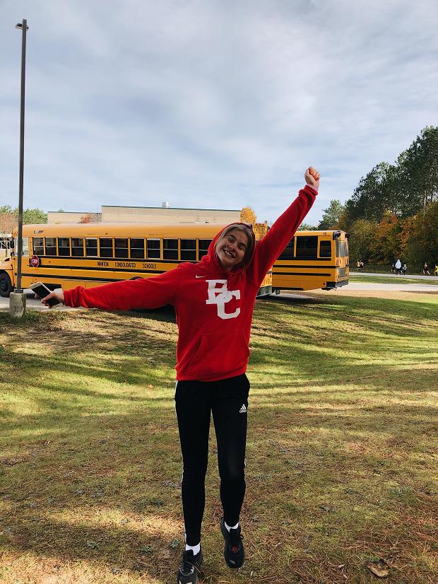 Utbytesstudent framför gul skolbuss