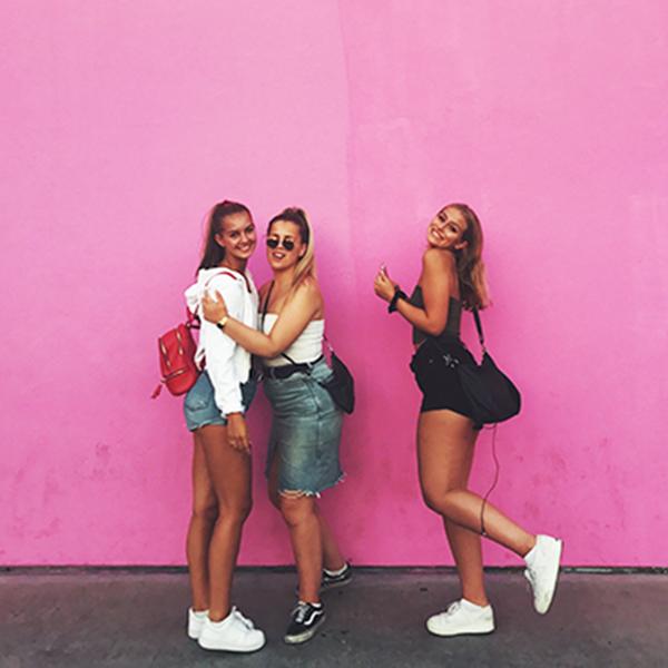 Tre exchange student con sfondo rosa