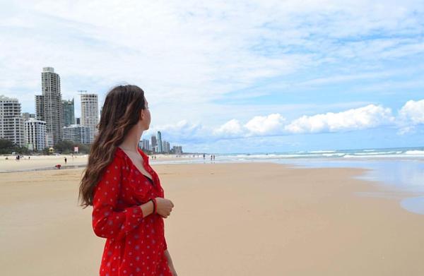 Exchange student sulla spiaggia dell'oceano Pacifico con indosso un vestito rosso