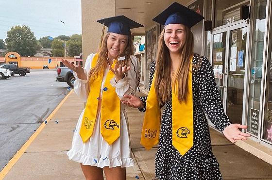 Zwei lächelnde Schülerinnen vor einer High School in den USA