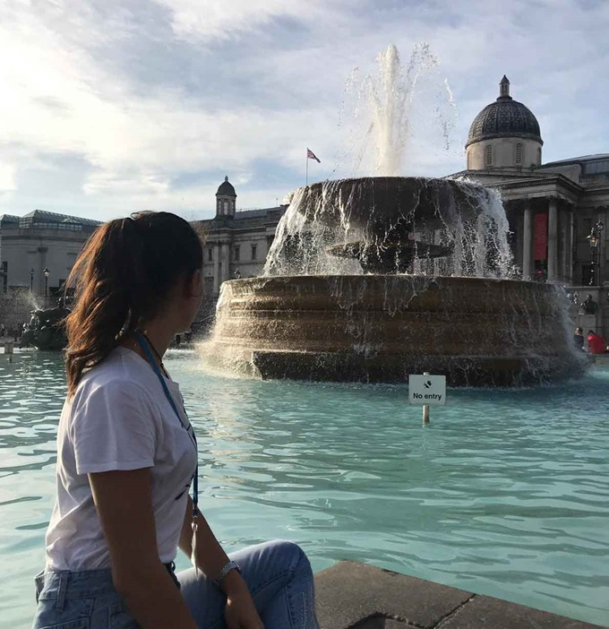 Student sitting next to a fountain, in London