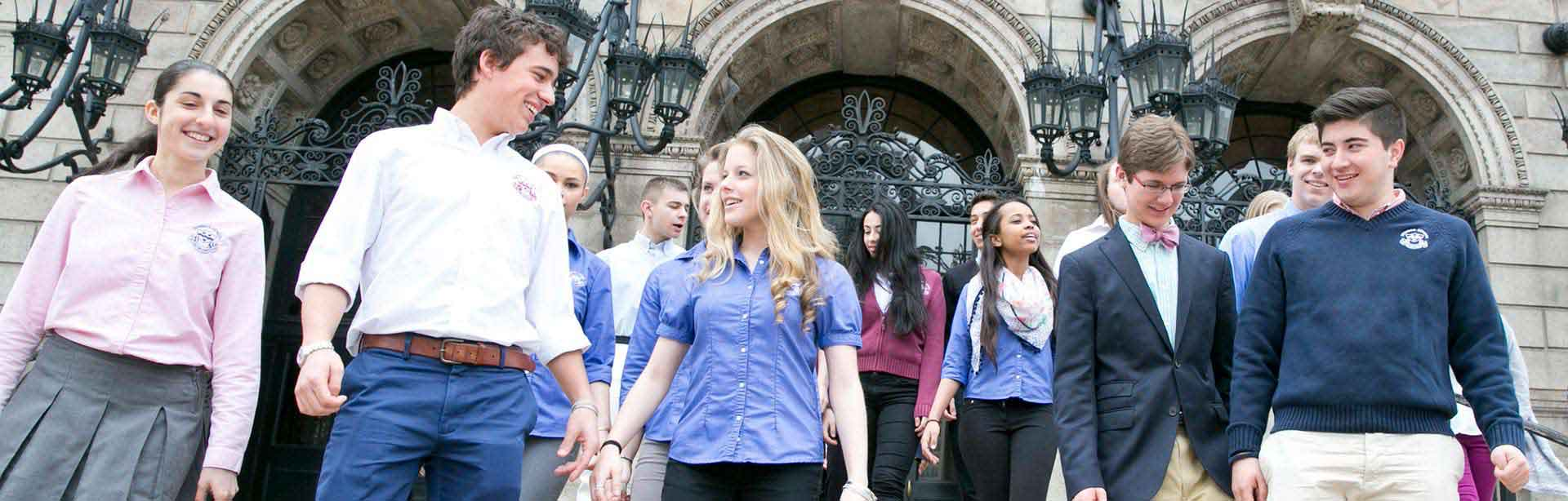 Students at the Newman School walk down the steps of the Boston Public Library